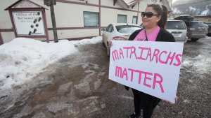 A pro-pipeline supporter holds a sign outside the Wet'suwet'en offices in Smithers, B.C., Thursday, February 27, 2020. A long-sought meeting between Wet'suwet'en hereditary chiefs and the federal and B.C. Indigenous relations ministers is underway in Smithers. THE CANADIAN PRESS/Jonathan Hayward