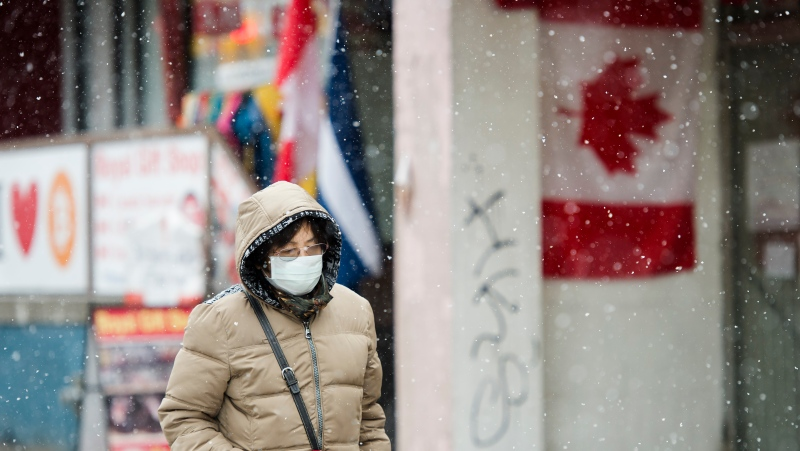 A pedestrian wears a protective mask as she walks in the winter weather downtown in Toronto on Wednesday, February 26, 2020. THE CANADIAN PRESS/Nathan Denette