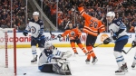 Winnipeg Jets goalie Connor Hellebuyck (37) is scored on as Edmonton Oilers' Leon Draisaitl (29) celebrates the goal during second period NHL action in Edmonton, Saturday, Feb. 29, 2020. THE CANADIAN PRESS/Jason Franson