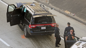 Los Angeles police officers stand after a pursuit of a stolen hearse with with a casket and body inside on Interstate 110 in South Los Angeles Thursday, Feb. 27, 2020. (AP Photo/Reed Saxon)