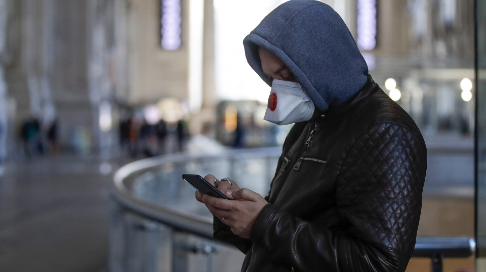 A man wearing a sanitary mask holds a smartphone at the Centrale main railway station in Milan, Italy, Monday, Feb. 24, 2020. (AP Photo/Luca Bruno)