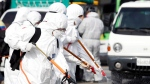 Workers wearing protective gears spray disinfectant as a precaution against the coronavirus at a bus garage in Gwangju, South Korea, Tuesday, March 3, 2020. China's coronavirus caseload continued to wane Tuesday even as the epidemic took a firmer hold beyond Asia. (Shin Dae-hee/Newsisvia AP)