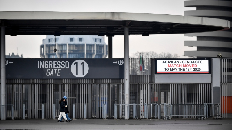 People walk outside San Siro stadium where a notice advising that the Serie A soccer match between AC Milan and Genoa is postponed to May 13, 2020, in Milan, Italy, Sunday, March 1, 2020. (Claudio Furlan/LaPresse via AP)