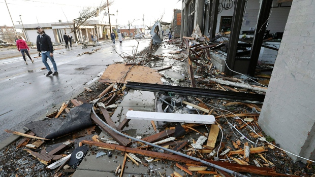 People pass by businesses destroyed by storms Tuesday, March 3, 2020, in Nashville, Tenn. (AP Photo/Mark Humphrey)