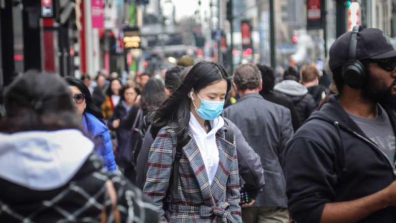 A pedestrian wears a surgical mask on a busy street in mid-town Manhattan, as concerns grow around COVID-19, Tuesday March 3, 2020, in New York. (AP / Bebeto Matthews)