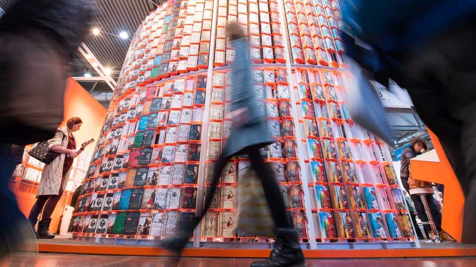 FILE --- In this Thursday, March 15, 2018 photo visitors walk past a booth in one of the exhibition halls during the opening day at the Leipzig International Book Fair in Leipzig, Germany. (AP Photo/Jens Meyer)