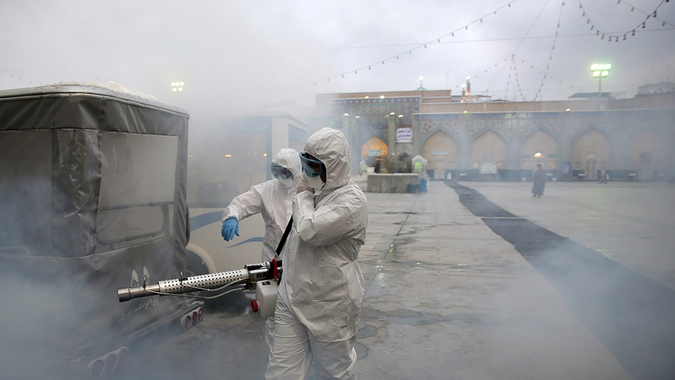 Members of the medical team spray disinfectant to sanitize outdoor place of Imam Reza's holy shrine, following the coronavirus outbreak, in Mashhad, Iran February 27, 2020. Picture taken February 27, 2020. (West Asia News Agency via Reuters)
