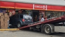 A tow truck prepares to remove an SUV that crashed into a Circle K store in Windsor. (Ricardo Veneza / CTV Windsor)