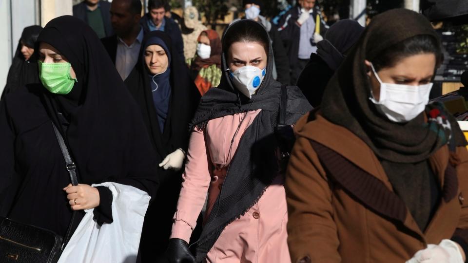 People wearing face masks walk on a sidewalk in downtown Tehran, Iran, Monday, March 2, 2020. (AP Photo Vahid Salemi)
