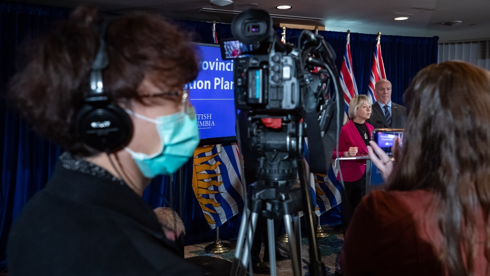 A camera operator wears a protective mask as provincial health officer Dr. Bonnie Henry responds to questions while B.C. Premier John Horgan, back right, listens during a news conference about the provincial response to the coronavirus, in Vancouver, on Friday, March 6, 2020. THE CANADIAN PRESS/Darryl Dyck