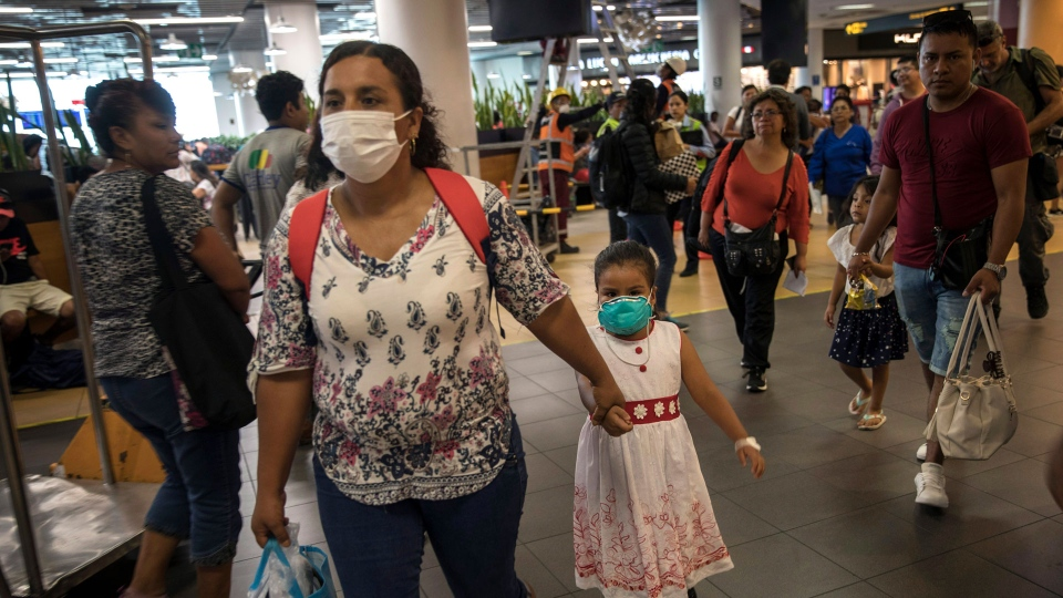 Wearing masks, passenger Gladys Ruiz Torres walks with her daughter Natali Oliva to the departure lounge at the international airport in Lima, Peru, Friday, March 6, 2020.  (AP / Rodrigo Abd)