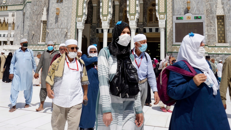 Muslim worshippers wear masks after the noon prayers outside the Grand Mosque, in the Muslim holy city of Mecca, Saudi Arabia, Saturday, March 7, 2020. (AP Photo/Amr Nabil)
