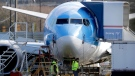 In this March 13, 2019, file photo, workers walk past a Boeing 737 MAX 8 airplane being built at Boeing Co.'s Renton Assembly Plant in Renton, Wash. (AP Photo/Ted S. Warren, File)