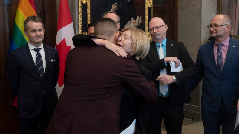 Natural Resources Minister Seamus O'Regan (left), NDP MP Randall Garrison and Minister of Justice and Attorney General of Canada David Lametti look on as survivor Matt Ashcroft hugs Cheri DiNovo during an announcement on Parliament Hill in Ottawa, Monday March 9, 2020. THE CANADIAN PRESS/Adrian Wyld