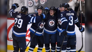 Winnipeg Jets' Cody Eakin, centre, celebrates his goal against the Arizona Coyotes with Patrik Laine, left to right, Nikolaj Ehlers (27), Nathan Beaulieu (88) and Tucker Poolman (3) during third period NHL action in Winnipeg on Monday, Mar. 9, 2020. THE (Source: The Canadian Press/Fred Greenslade)