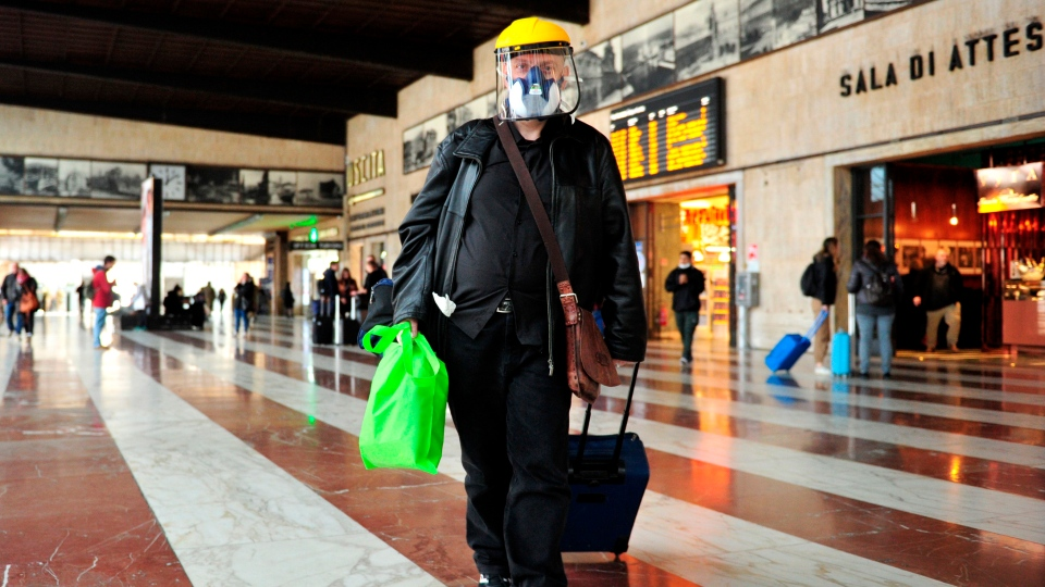 A man wears a mask as he walks in the train station in Florence, Italy, Tuesday, March 10, 2020. (Jennifer Lorenzini/LaPresse via AP)