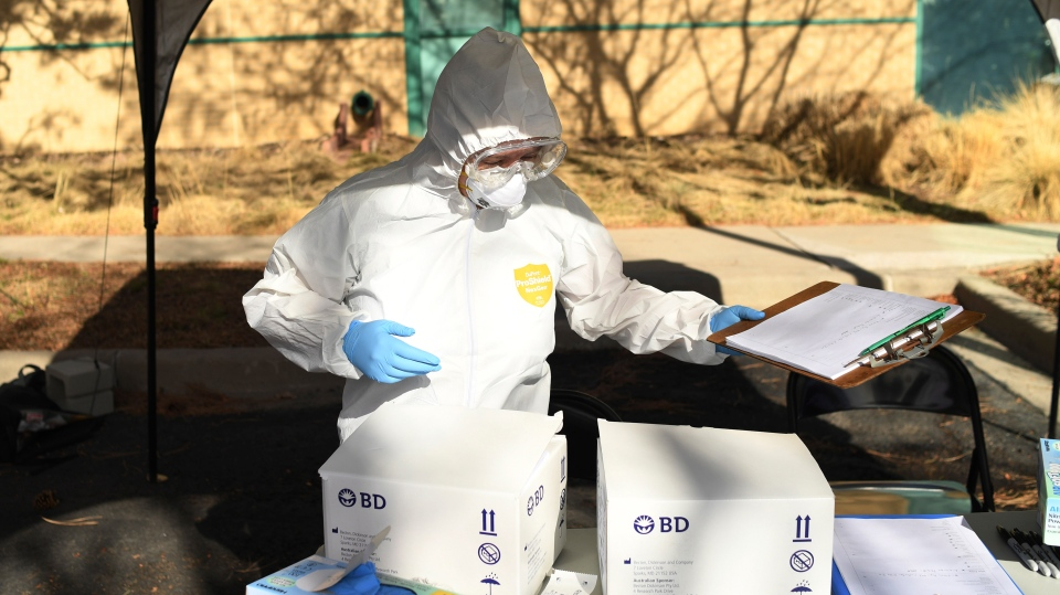 A woman sets up for the Colorado Department of Public Health and Environment first community testing center for COVID-19 at the state lab on Wednesday, March 11, 2020 in Denver, Colo.  (RJ Sangosti/The Denver Post via AP)