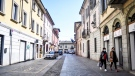 Two women walk in the town of Codogno, in the region of Lombardia, northern Italy, Wednesday, March 11, 2020. (Claudio Furlan/LaPresse via AP)