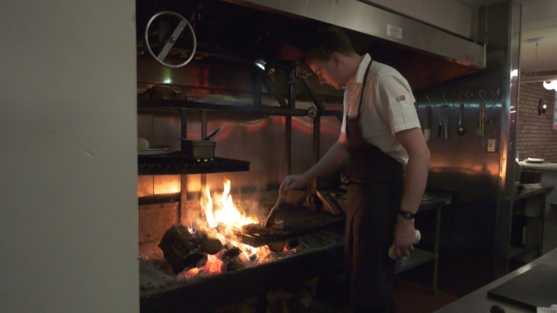 A chef cooking pork chops at Smokey Bear. March 11, 2020. (CTV News Edmonton)