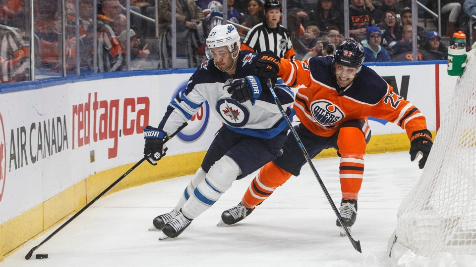 Winnipeg Jets' Nicholas Shore (21) is chased by Edmonton Oilers' Riley Sheahan (23) during third period NHL action in Edmonton, Alta., on Wednesday March 11, 2020. (THE CANADIAN PRESS/Jason Franson)