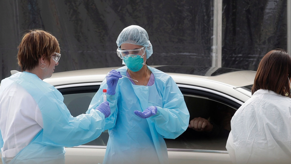 Health care personnel test a person in the passenger seat of a car for coronavirus at a Kaiser Permanente medical center parking lot in San Francisco, Thursday, March 12, 2020. (AP Photo/Jeff Chiu)