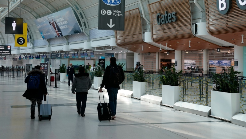 Travellers walk through Terminal 3 at Pearson International Airport in Toronto, Friday, March 13, 2020.