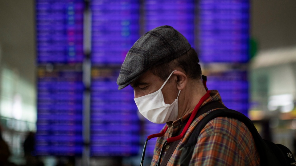 A man looks at his phone in front of the information screen at Barcelona airport, Spain, Thursday, March 12, 2020. (AP Photo/Emilio Morenatti)
