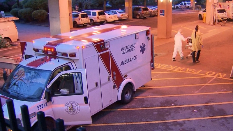 An ambulance is seen with first responders in protective gear outside a Vancouver hospital on March 12, 2020.
