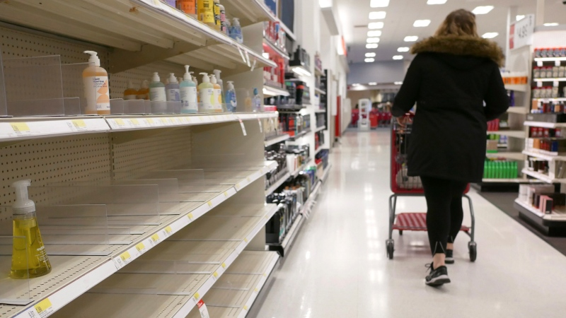 In this March 3, 2020 file photo, shelves that held hand sanitizer and hand soap are mostly empty at a Target in Jersey City, N.J. People who may have been exposed to the new coronavirus or who get sick with COVID-19 may be advised to stay home for as long as 14 days to keep from spreading it to others, according to the Centers for Disease Control. That's led many people to wonder if they could manage for two weeks at home without a run to the grocery store. (AP Photo/Seth Wenig)