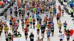 In this file photo on April 17, 2017, runners in the 121st Boston Marathon head down the stretch to the finish line in Boston. (AP Photo/Charles Krupa, File)