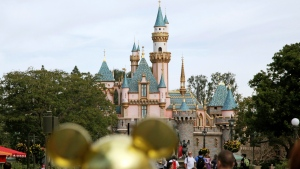 In this Jan. 22, 2015, file photo, visitors walk toward Sleeping Beauty's Castle in the background at Disneyland Resort in Anaheim, Calif. Disneyland says it's closing its California parks starting Saturday over coronavirus concerns. For most people, the new coronavirus causes only mild or moderate symptoms. For some it can cause more severe illness. (AP Photo/Jae C. Hong, File)