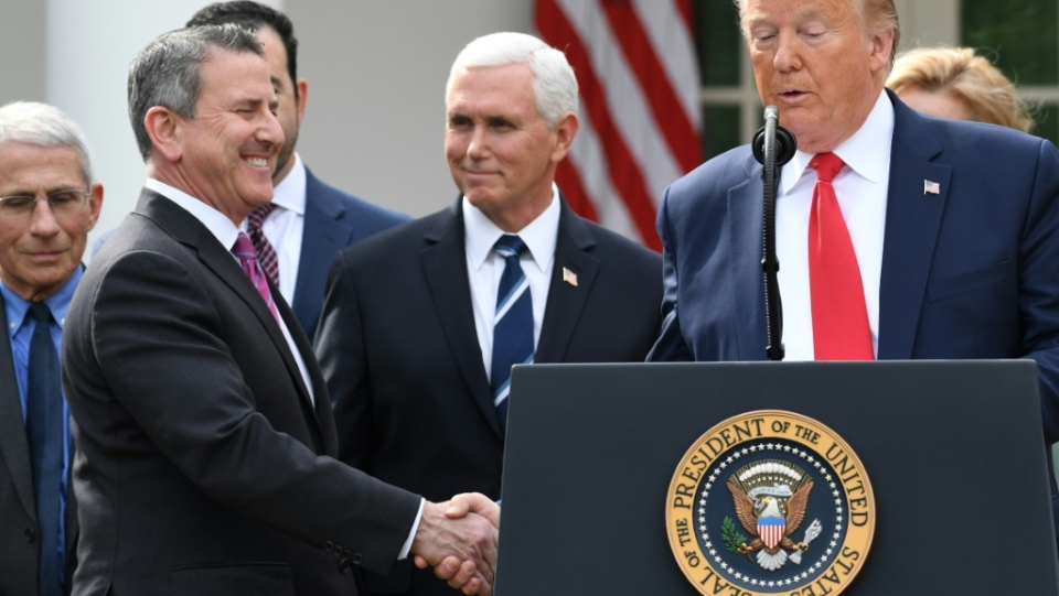 U.S. President Donald Trump shakes hand with Brian Cornell, CEO of Target, at a White House event on preventing spread of the coronavirus. (Source: AFP)