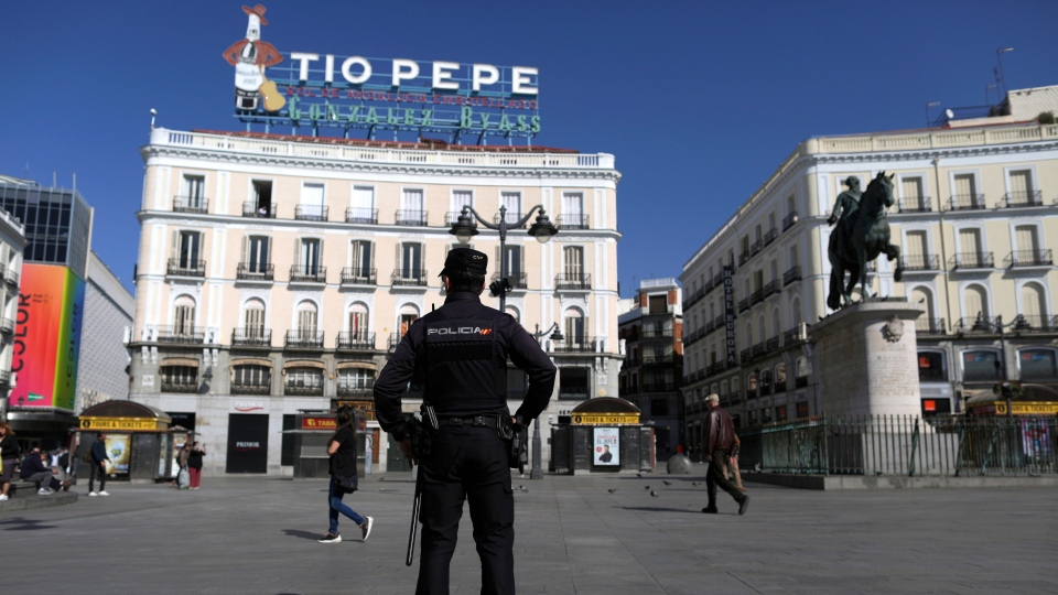 A police officer stands guard at Sol square in downtown Madrid, Spain, Saturday, March 14, 2020. (AP Photo/Manu Fernandez)