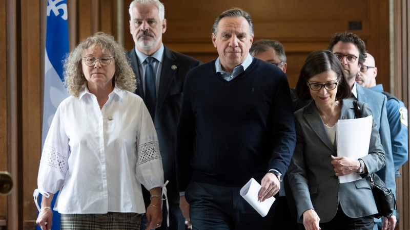 Quebec Premier Francois Legault, flanked by Quebec Minister Responsible for Seniors and Informal Caregivers Marguerite Blais, left, and Quebec Health Minister Danielle McCann, walk to a daily news conference, Saturday, March 14, 2020 at the legislature in Quebec City. THE CANADIAN PRESS/Jacques Boissinot