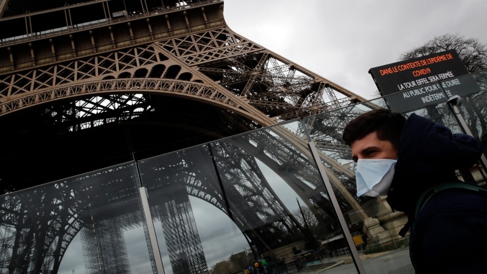 A man wearing a mask walks pasts the Eiffel tower closed after the French government banned all gatherings of over 100 people to limit the spread of the virus COVID-19, in Paris, Saturday, March 14, 2020. (AP Photo/Christophe Ena)