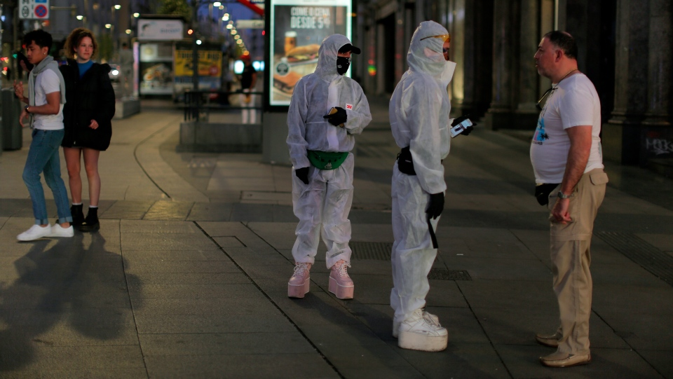 People wearing protective clothes talk with a man at the Gran Via avenue in downtown in Madrid, Spain, Saturday, March 14, 2020. (AP Photo/Manu Fernandez)