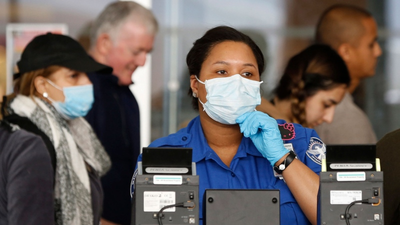 A Transportation Security Administration (TSA) employee adjusts her face mask while screening passengers entering through a checkpoint at John F. Kennedy International Airport, Saturday, March 14, 2020, in New York. The American Academy of Family Physicians recommends workers without insurance contact a local health department or community health center for help. (AP Photo/Kathy Willens)