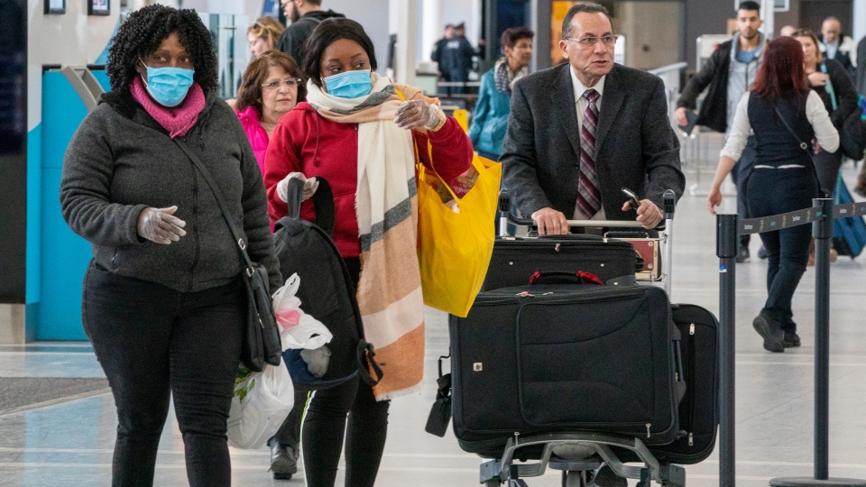 Passengers wear masks and gloves as they arrive for their flight at Pearson Airport in Toronto on Friday, March 13, 2020. THE CANADIAN PRESS/Frank Gunn