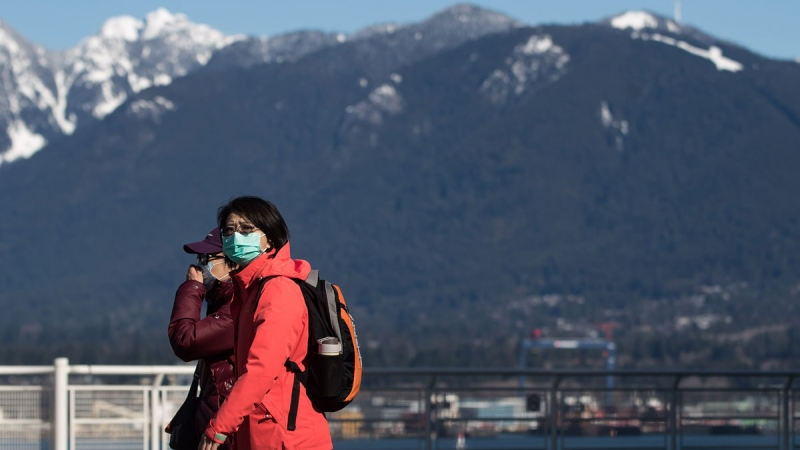 People wearing protective face masks walk on a nearly deserted plaza outside Canada Place, in Vancouver, on Saturday, March 14, 2020. THE CANADIAN PRESS/Darryl Dyck