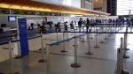 The check-in line for British Airways is empty at the Los Angeles International Airport Sunday, March 15, 2020, in Los Angeles. (AP Photo/Marcio Jose Sanchez)