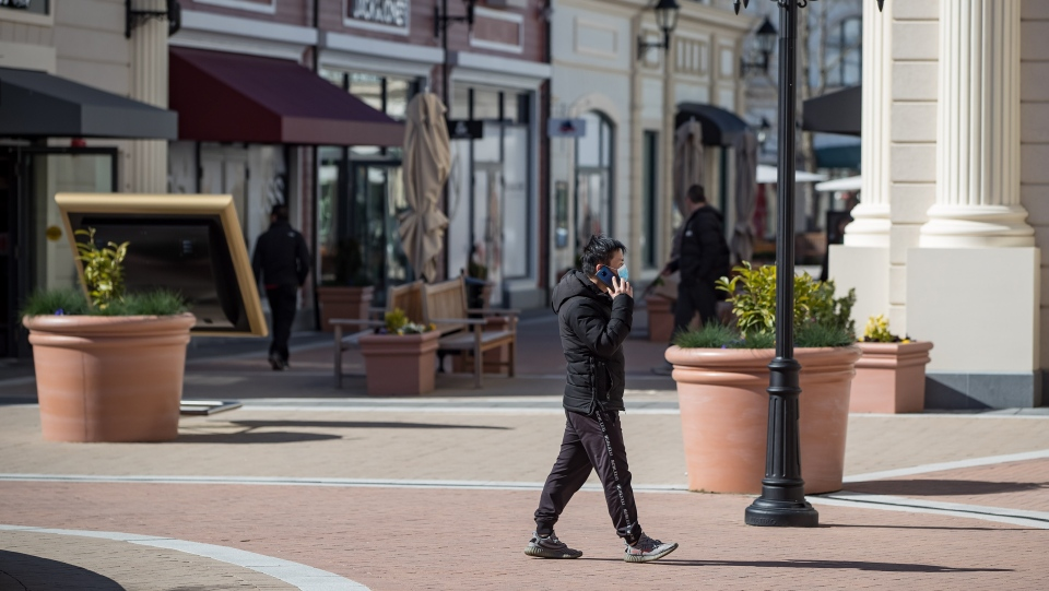 A man wearing a protective face mask walks through a sparsely occupied open-air shopping mall amid concerns about the coronavirus, in Richmond, B.C., on Sunday, March 15, 2020. THE CANADIAN PRESS/Darryl Dyck