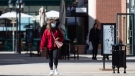 A woman wearing a protective face mask walks through a sparsely occupied open-air shopping mall amid concerns about the coronavirus, in Richmond, B.C., on Sunday, March 15, 2020. THE CANADIAN PRESS/Darryl Dyck