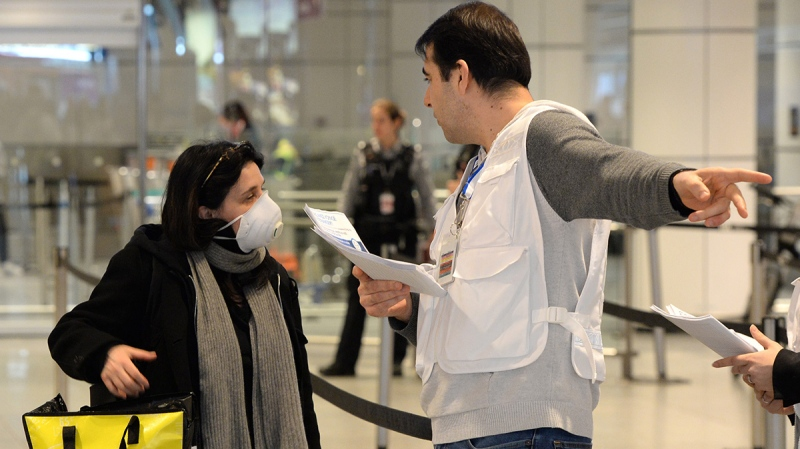 A Quebec health worker (right), assigned by the city of Montreal, greets passenger and hands out information on COVID-19 at Trudeau Airport in Montreal, Monday, March 16, 2020. THE CANADIAN PRESS/ Ryan Remiorz