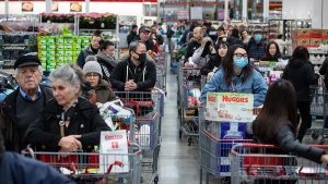 Some of the hundreds of people queued in multiple lines wait to pay for their purchases at a Costco store, amid concerns about the spread of the coronavirus, in Burnaby, B.C., on Monday, March 16, 2020. THE CANADIAN PRESS/Darryl Dyck