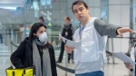 Quebec healthcare workers assigned by the city of Montreal hand out information pamphlets on COVID-19 procedures to passengers arriving from abroad at Trudeau International Airport on Monday, March 16, 2020 in Montreal. THE CANADIAN PRESS/Ryan Remiorz
