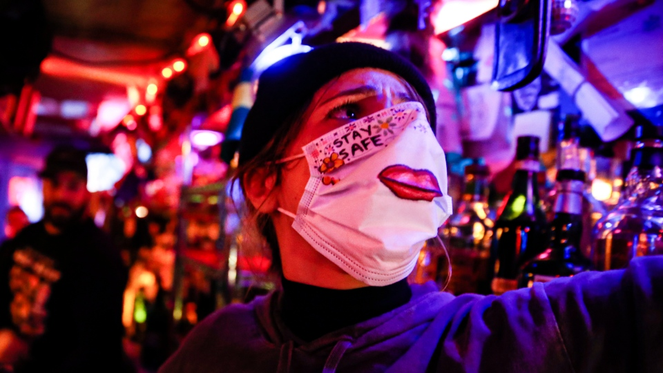 Bartender Cassandra Paris wears a protective face mask before taking a farewell shot at an early closing time at 169 Bar with patrons, Monday, March 16, 2020, in New York. (AP Photo/John Minchillo)
