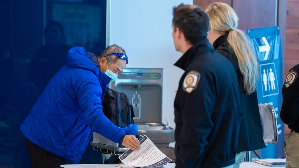 A man takes a pamphlet as public health inspectors greet passengers at Halifax Stanfield International Airport in Enfield, N.S. on Monday, March 16, 2020. The province has placed some restrictions on travellers in the effort to control the spread of COVID-19 in Nova Scotia. (THE CANADIAN PRESS/Andrew Vaughan)