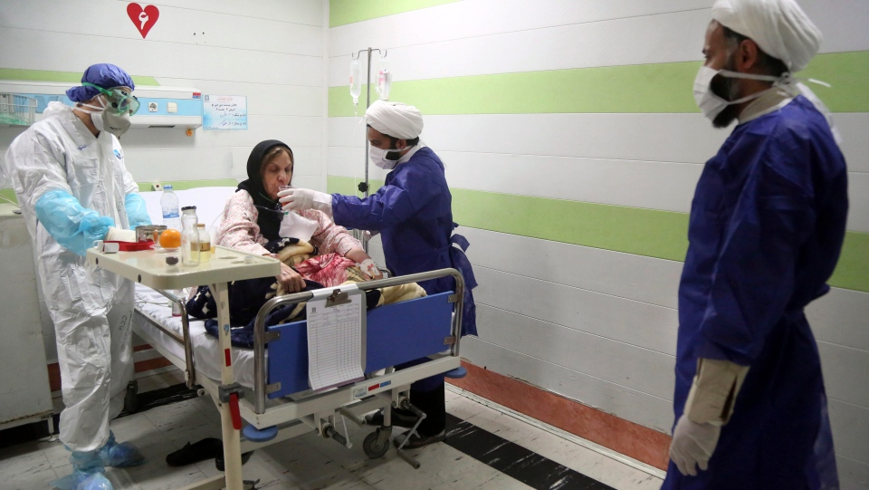 In this Saturday, March 7, 2020 file photo, a cleric, right, assists a medic treating a patient infected with the new coronavirus, at a hospital in Qom, about 80 miles (125 kilometers) south of the capital Tehran, Iran. (Mohammad Ali Marizad/Rasa News Agency via AP, File)