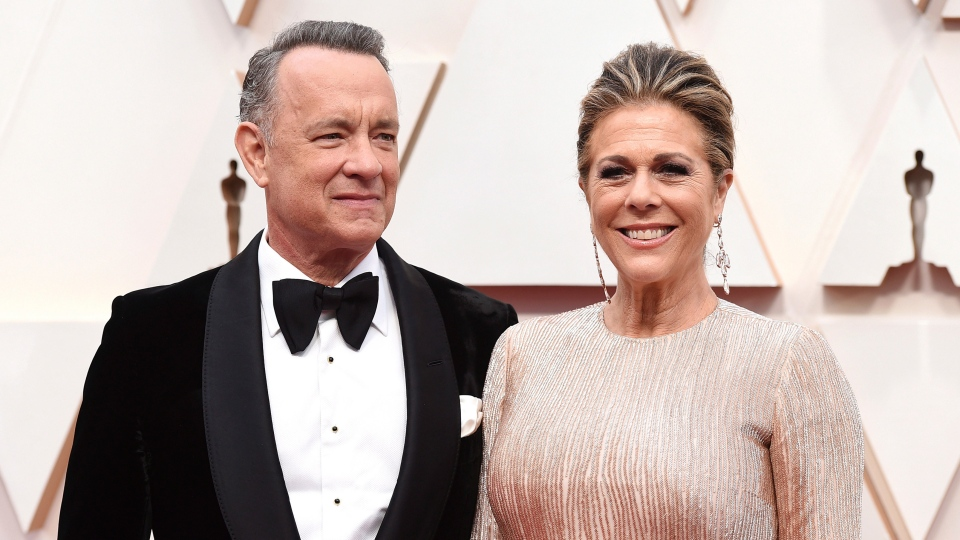 In this Sunday, Feb. 9, 2020 file photo, Tom Hanks, left, and Rita Wilson arrive at the Oscars at the Dolby Theatre in Los Angeles. (Jordan Strauss/Invision/AP)