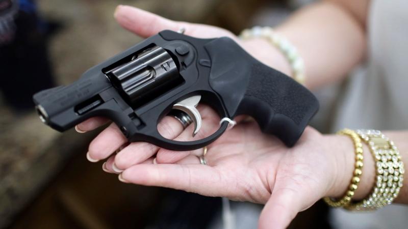 Haylee Romander shows off her new .357 magnum pistol at Ross Coin and Gun, Monday, March 16, 2020, in Idaho Falls, Idaho. R(John Roark/The Idaho Post-Register via AP)